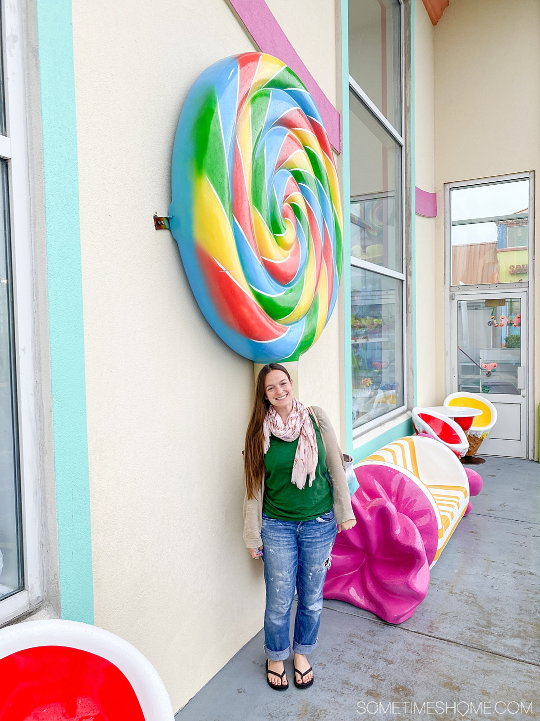 A woman standing in front of a colorful, oversized rainbow swirl lollipop in the Outer Banks of North Carolina.