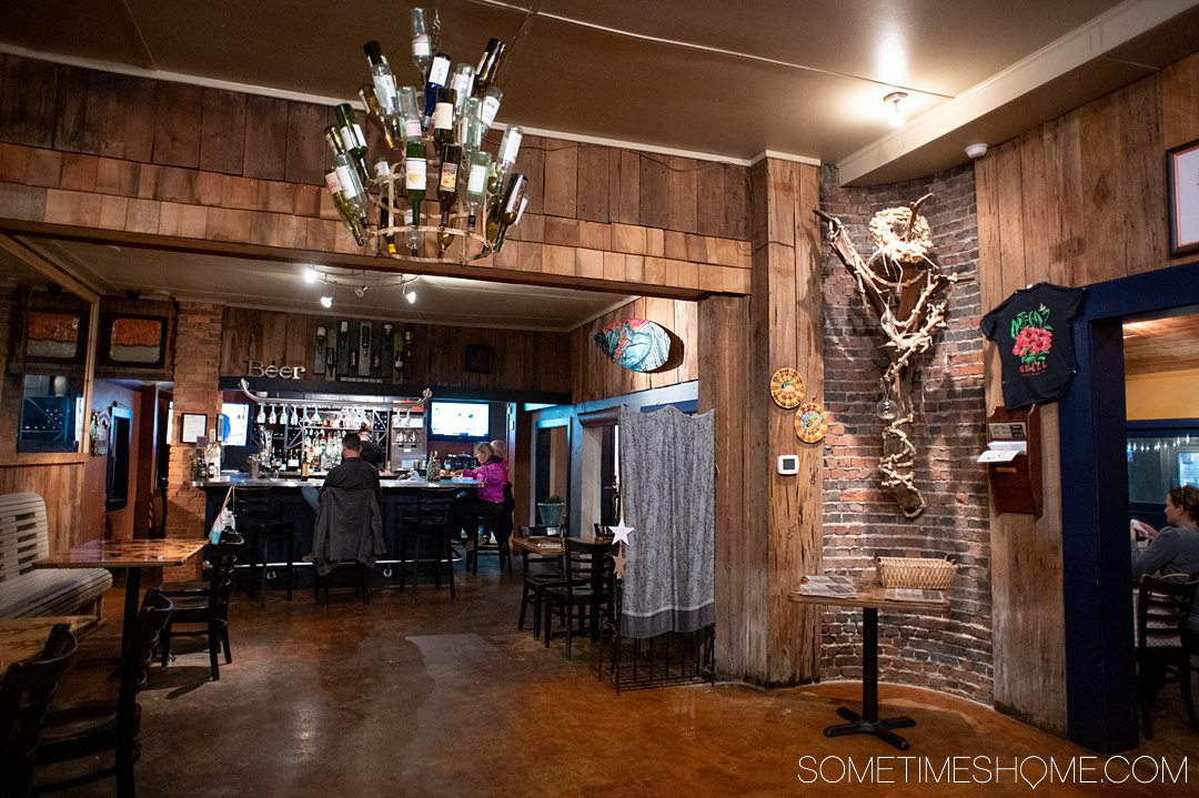 Inside of a restaurant with a wine bottle chandelier and wood finished walls and a dark floor. It's a great place to visit for one of the best Outer Banks indoor activities: drinking wine!