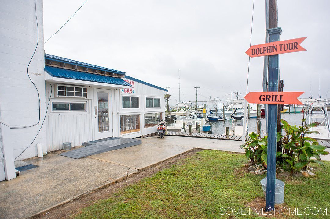 Signage at a waterfront restaurant at a marina to the white-painted restaurant with a blue roof.