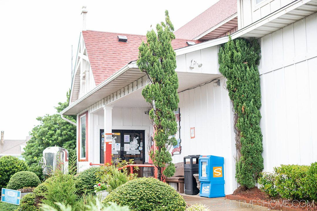 Photo of the exterior of a brewery in the Outer Banks of North Carolina with green trees out front of a white building.