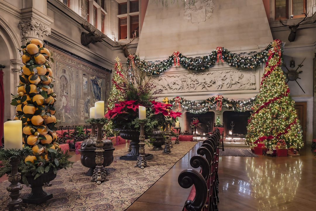 Interior of The Biltmore in Asheville, NC, decorated with garland and a Christmas tree.