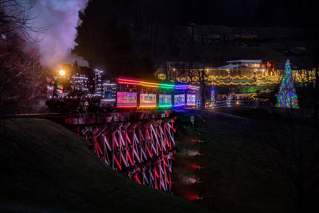 Illuminated train on a bridge above water at night with rainbow lights during a holiday winter event in NC.