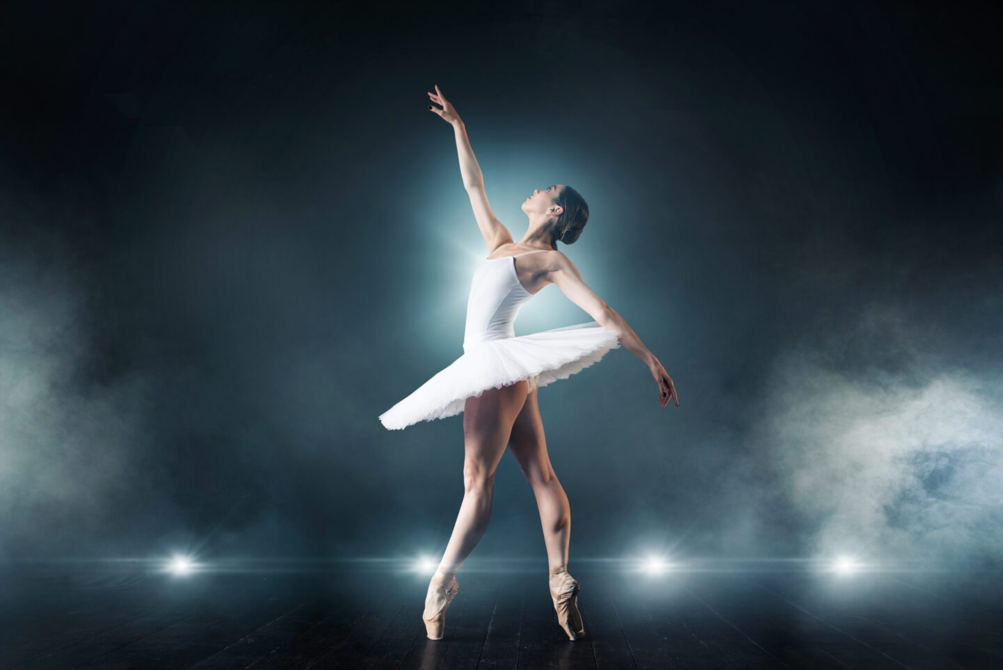 Ballet dancer in white dress dancing on the stage in theatre. Graceful ballerina training in class