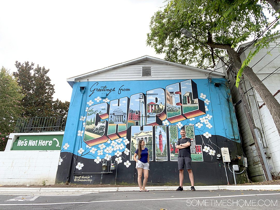"""A couple in front of a colorful mural that reads, """"Greetings from Chapel Hill."""""""