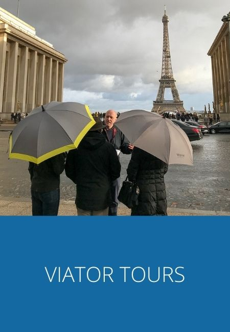 Viator Tours graphic with a photo of a tour in front of the Eiffel Tour with two people holding umbrellas.