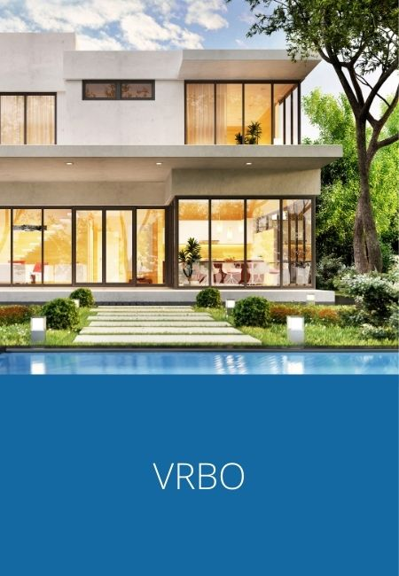 VRBO rentals with photo of a house with floor to ceiling windows illuminated with interior light.