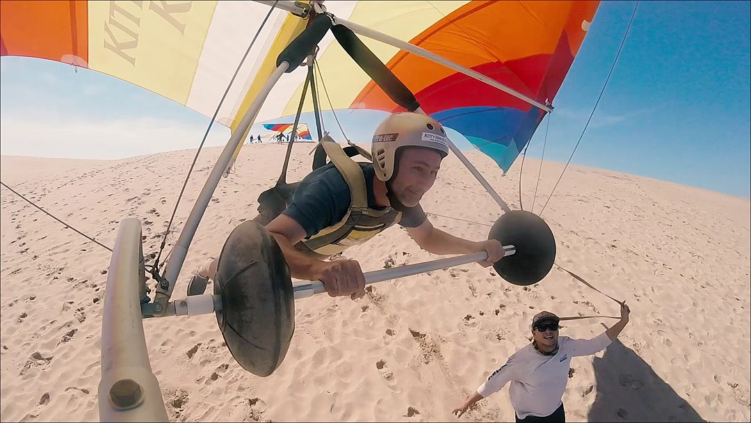 A man hang gliding with a gold helmet on in the Outer Banks in North Carolina.