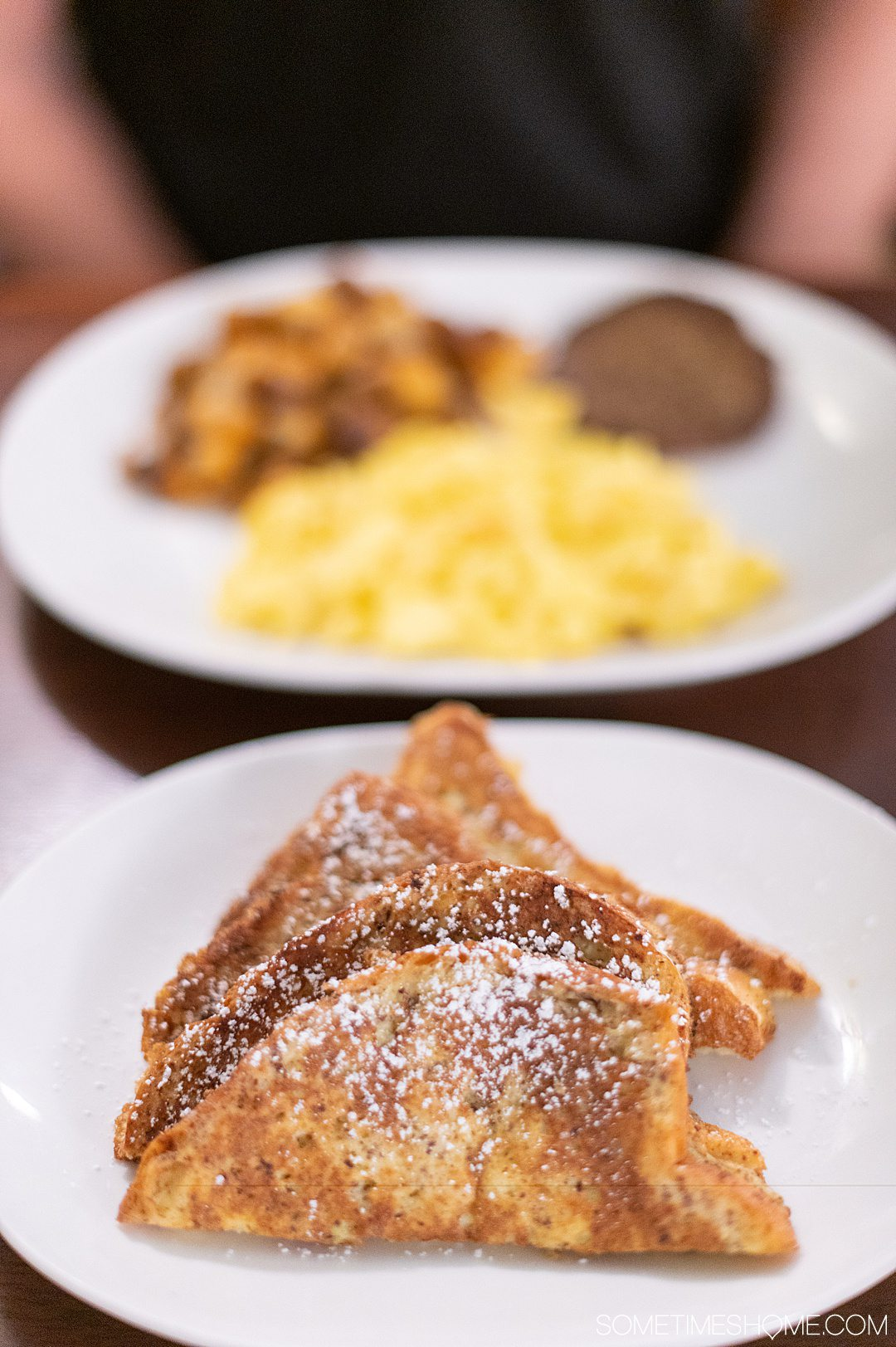 A plate of French toast in the foreground and eggs, potatoes and sausage blurry in the background.