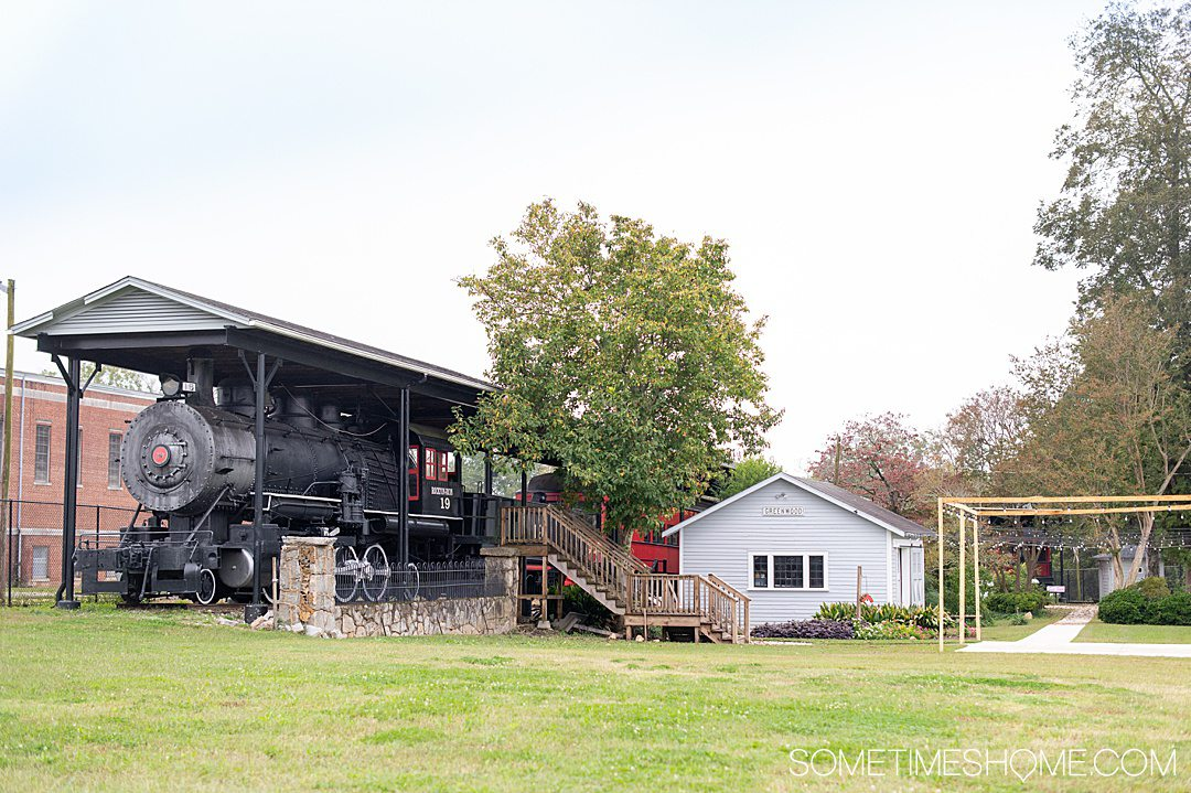 A locomotive on the left and small house structure on the right at a historical Railroad center in Greenwood, South Carolina in the historic Old Ninety Six district.