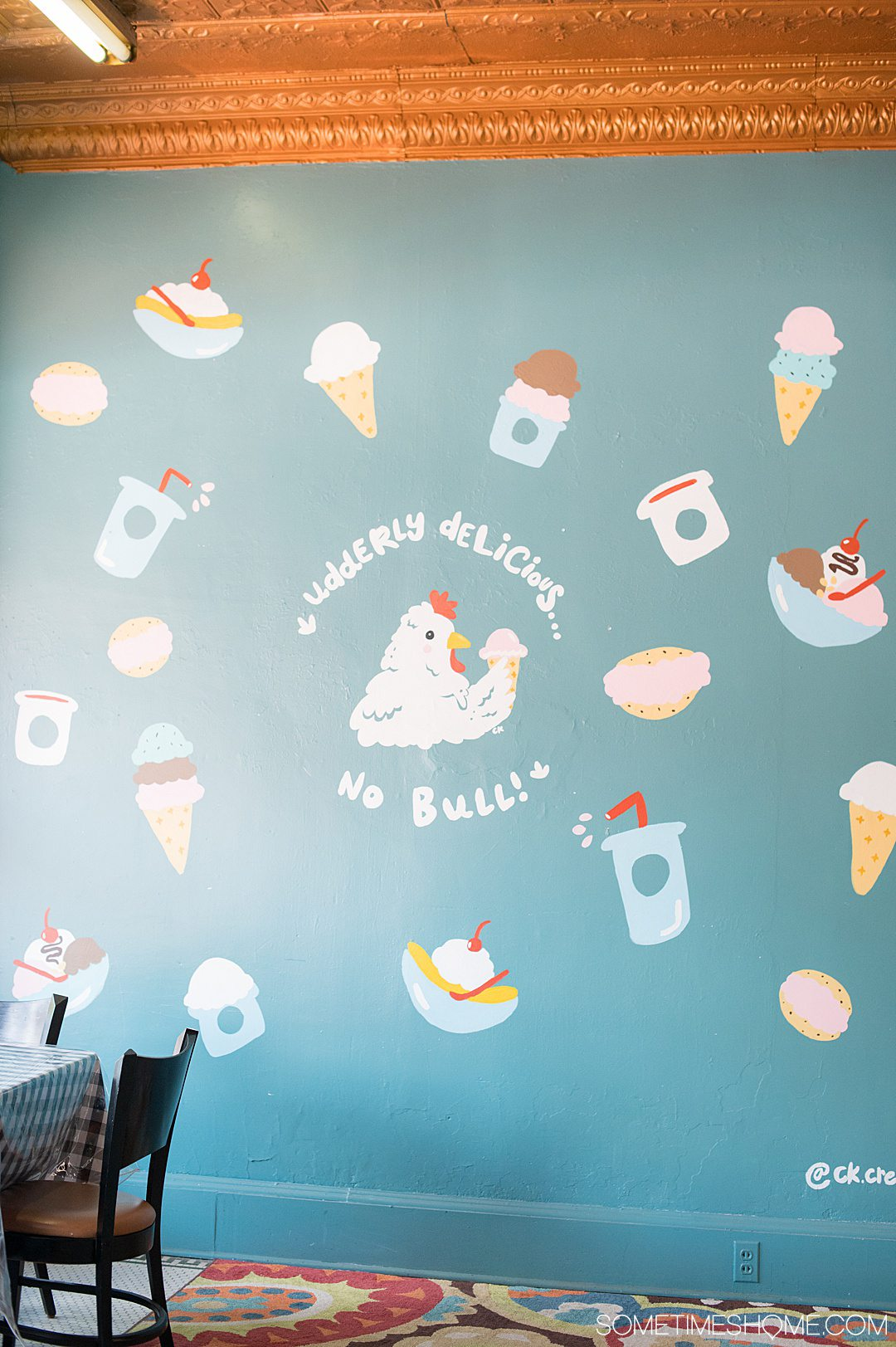 A blue wall with ice cream icons and a chicken painting in the middle at Chilly Chicken Creamery in Warrenton, NC.