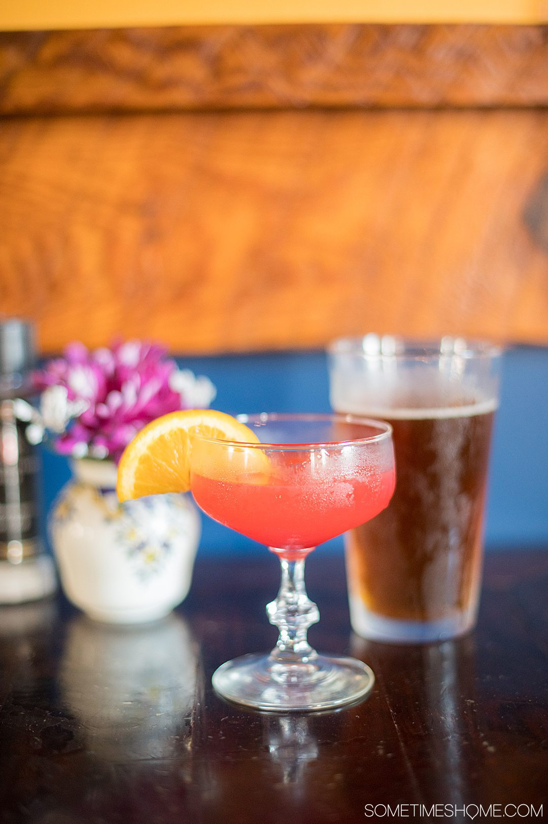 A pink drink in a martini glass with an orange slice and pour pint of draught beer behind it at Robinson Ferry in Warrenton, NC.