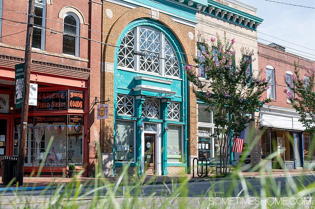 Brick building with shops in Warrenton, NC. The blue arch store is Drip Coffee + Market on Main Street downtown.