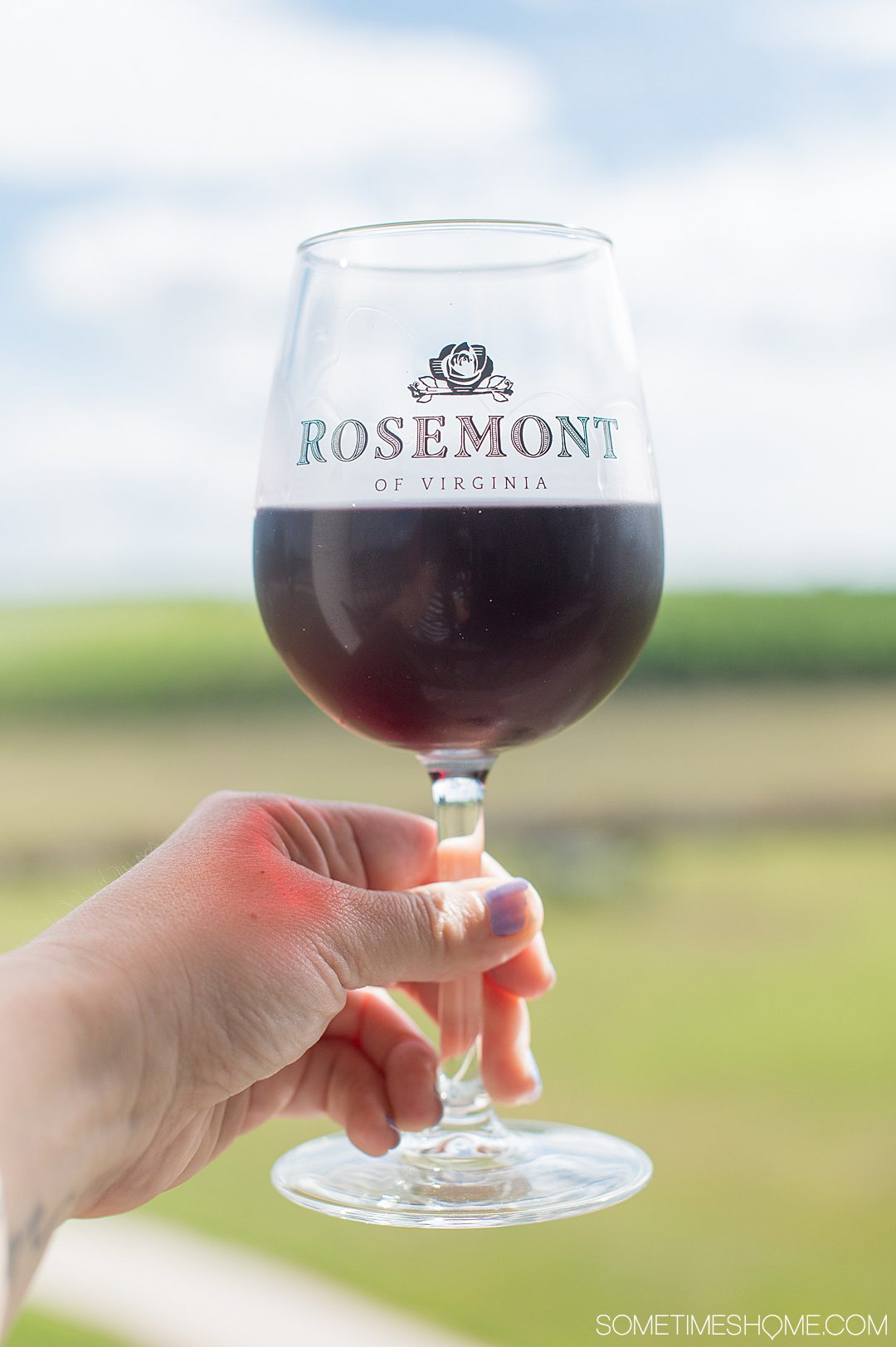 Rosemont vineyard wine glass with red wine and a woman's hand holding it against a blurry background of greenery in Virginia.