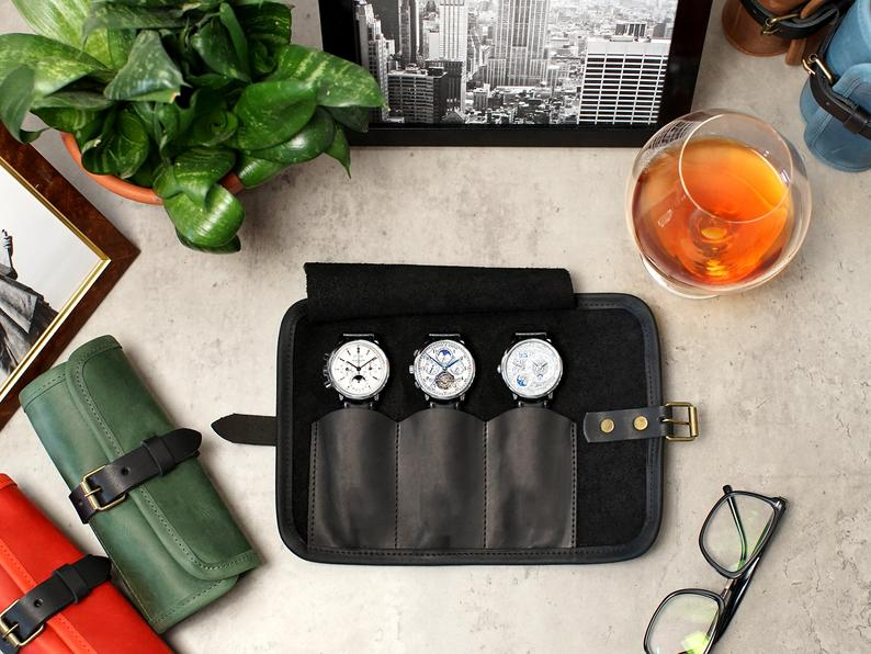 Watch roll with three watches, glasses nearby and a glass of bourbon from an overhead view.