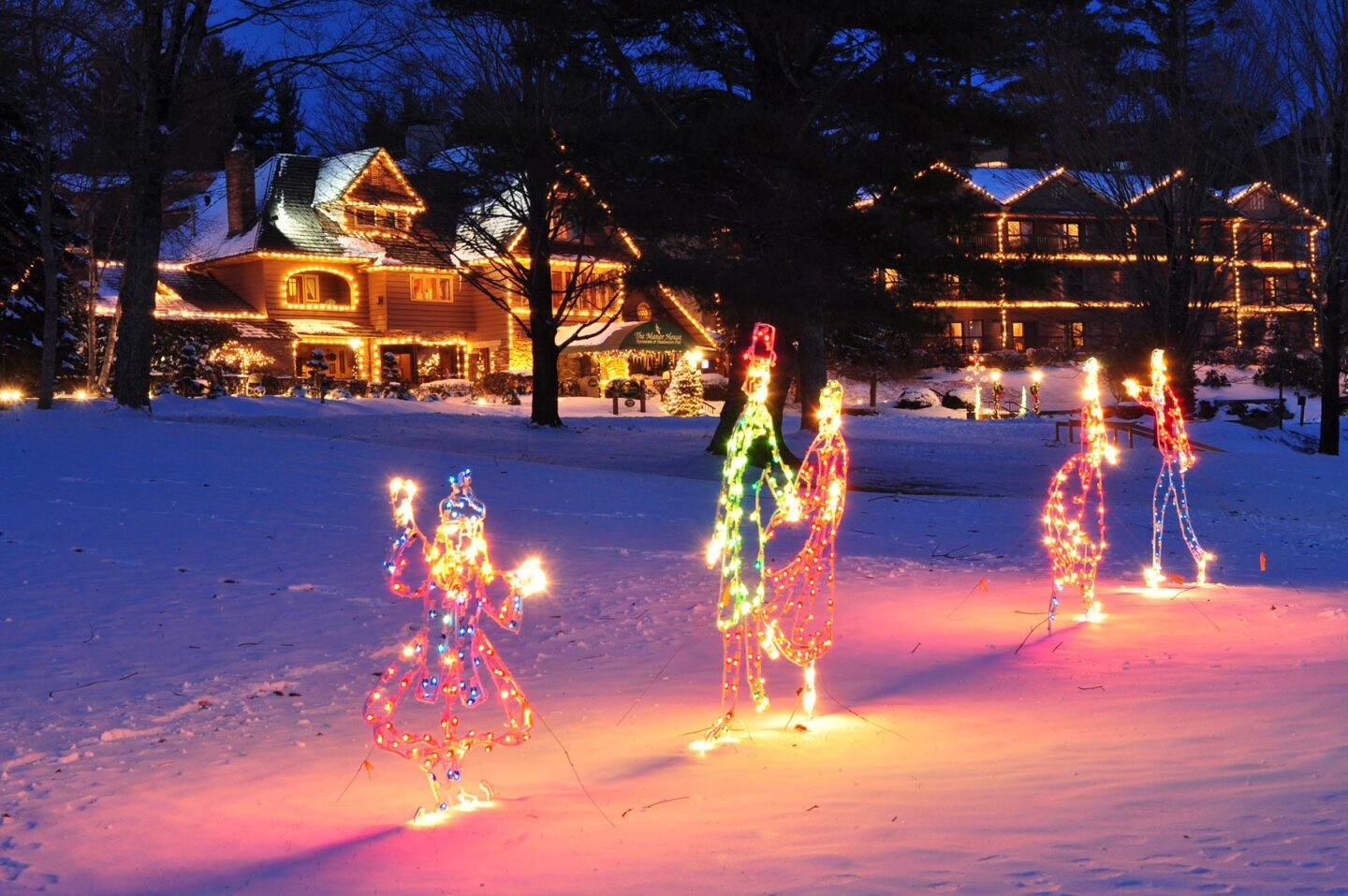 Holiday lights in the shape of people in the snow with a house with white Christmas lights in the background. Visiting Chetola Resort in Blowing Rock is one of the great winter events in North Carolina.