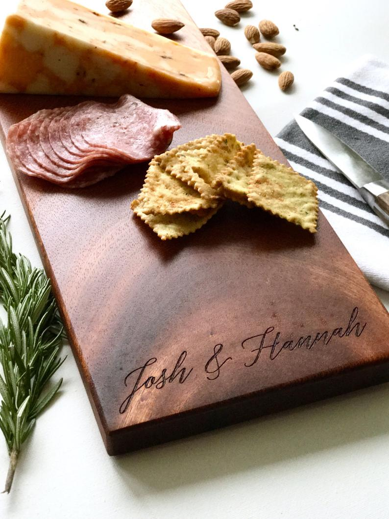 Wood cheese board customized with a name lasered on it for practical house warming gift ideas.