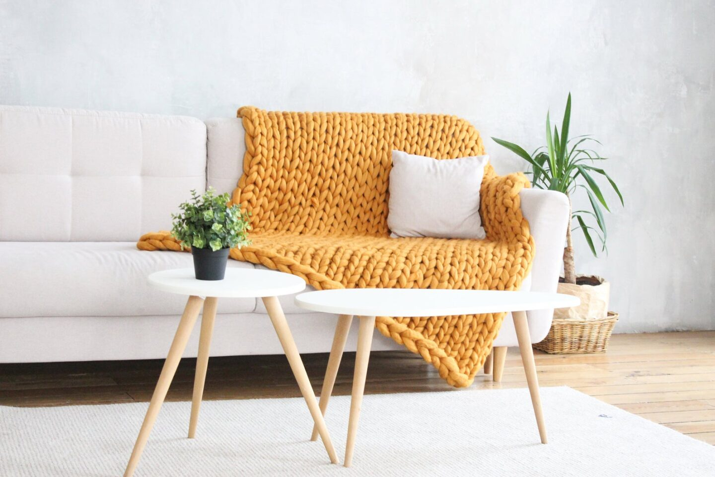 Yellow chunky knit throw blanket on a white couch with white tables in front of it via Etsy.