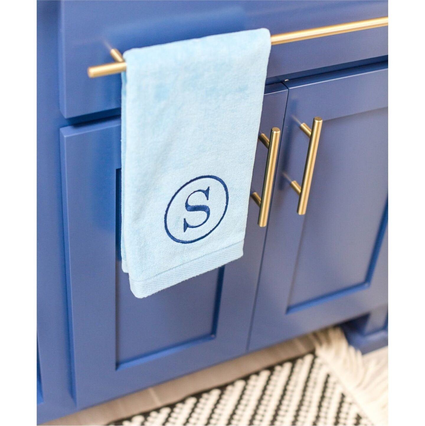 """Light blue hand towel with an """"S"""" monogram in a circle in dark blue embroidered thread."""