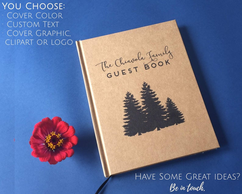 Custom handmade journal with silhouettes of three evergreen trees on kraft paper against a blue background for unique house warming gift ideas.