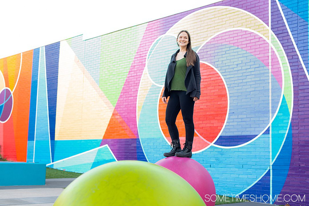 Woman on top of a large pink ball in black leggings, green top and black cardigan, with a colorful background with geometric shapes.