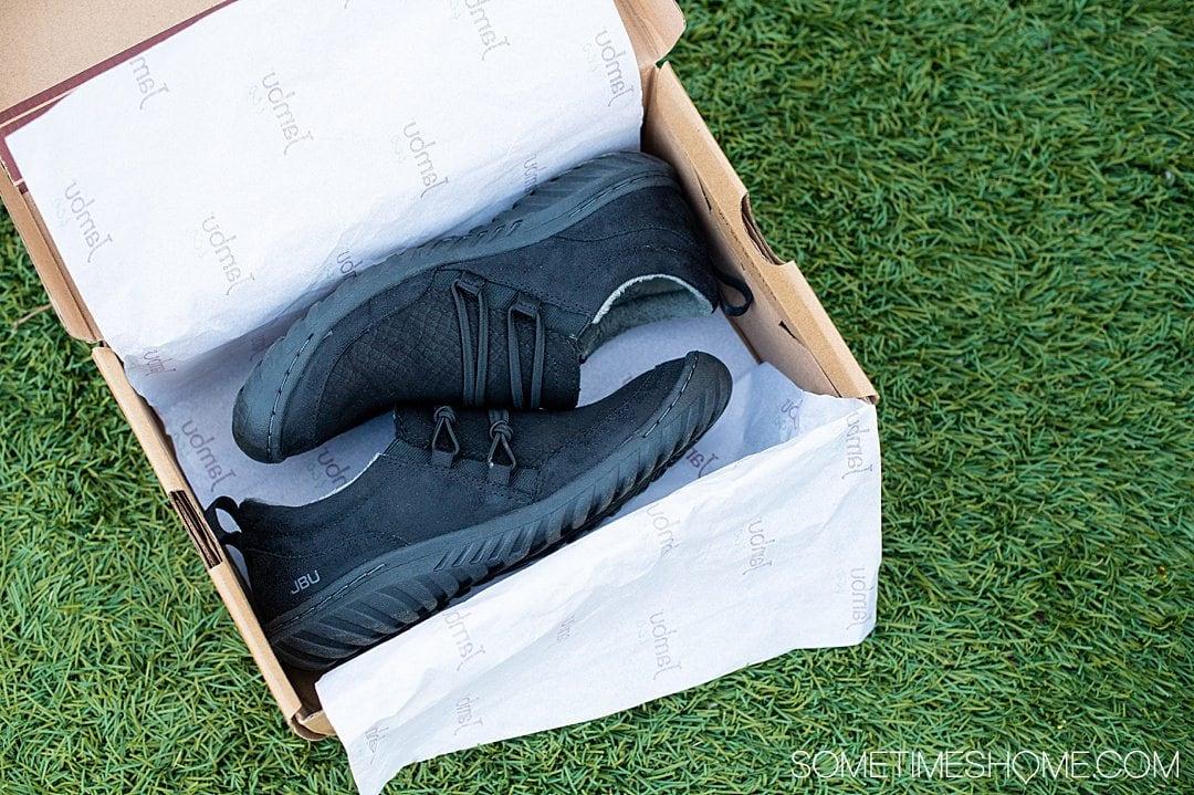 Pair of black Ashton Jambu & Co. shoes in a shoe box on grass.