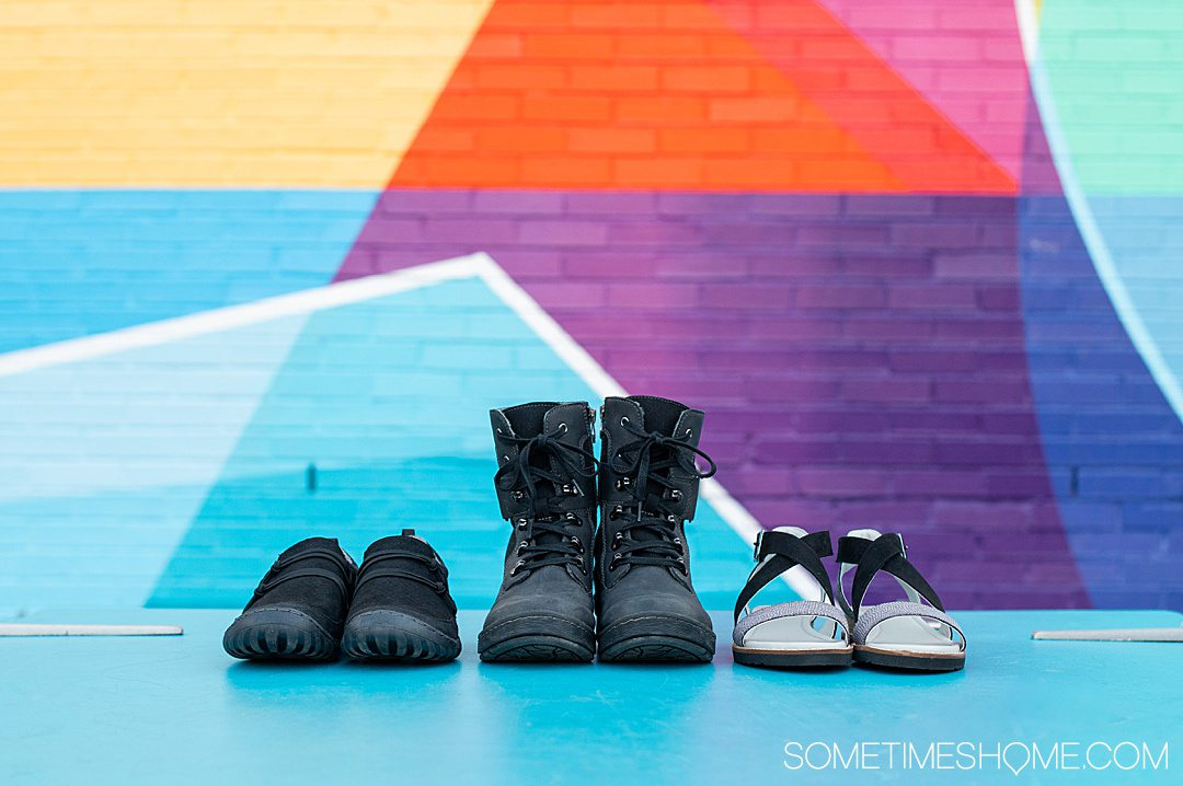 Three pairs of women's Jambu & Co. shoes in a row, in black, against a colorful background.