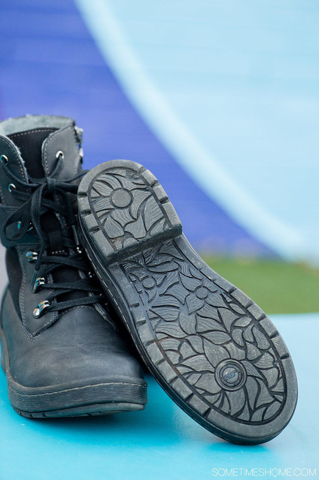 Decorative soles and laced-up front of a black pair of combat-inspired Jambu & Co. boots against a colorful background.