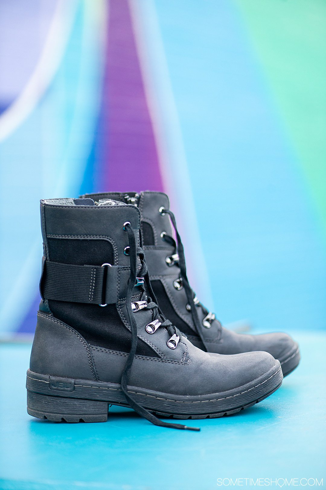 Black pair of combat-inspired Jambu & Co. boots against a colorful background.