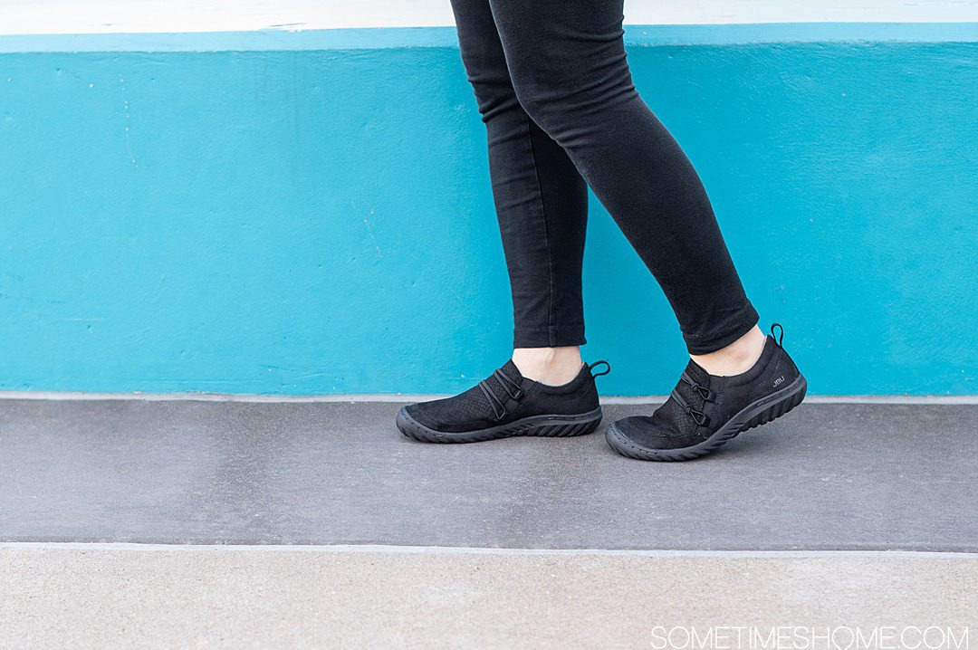 Black pair of women's flat Jambu shoes against a blue background and sidewalk for a review.