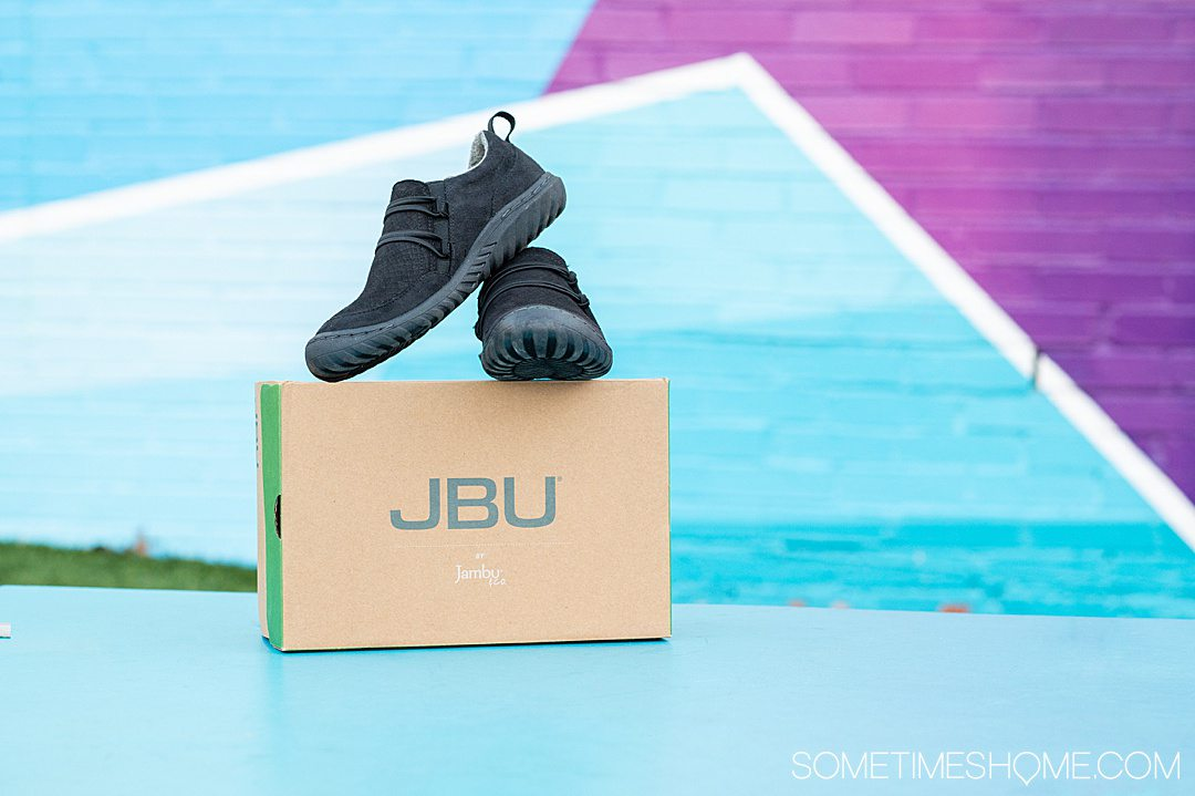 Black flat shoes from Jambu & Co. on the craft colored, recycled shoe box against a colorful background.