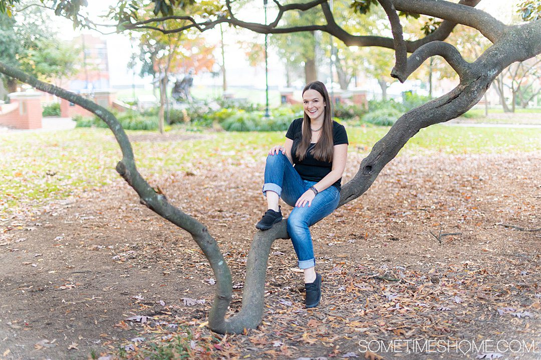 Women sitting on a tree branch in jeans and a black top, with Jambu & Co. pair of Ashton flat black shoes on.