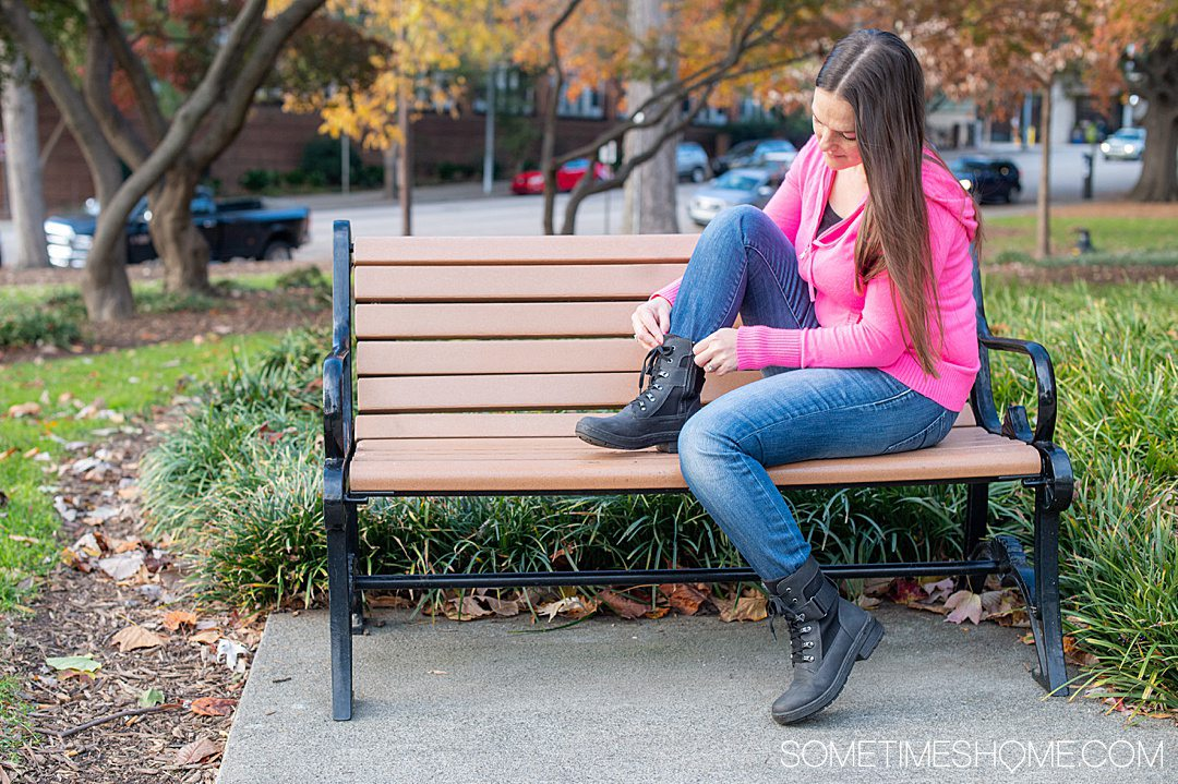 Woman sitting on a bench in blue jeans and a hot pink sweater hoodie with black combat-boot inspired shoes on from Jambu & Co.