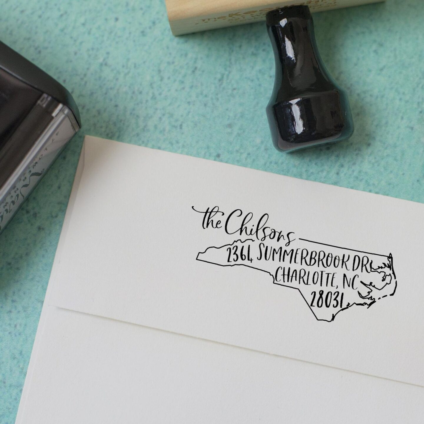 Custom return address stamp in the shape of the state of North Carolina, stamped on the back flap of an envelope.