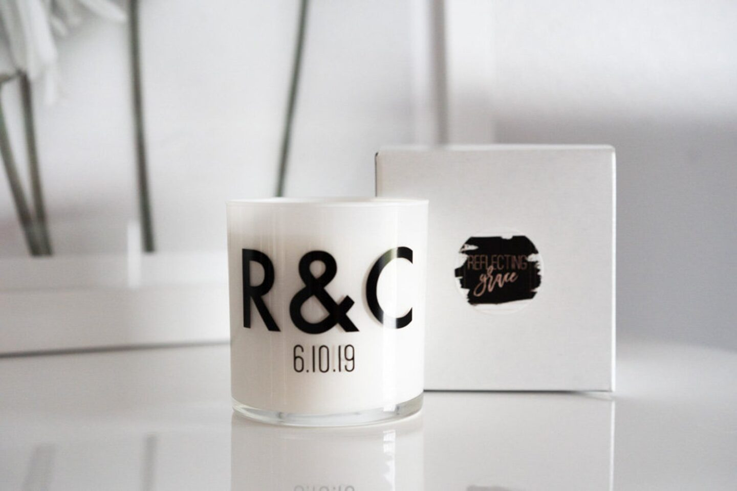Modern block letters monogram on a candle that says R&C in black against a white glass candle.