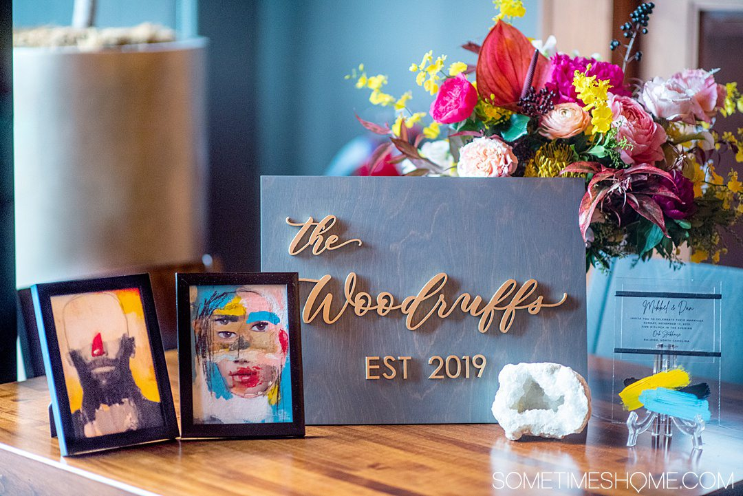 Grey and gold wooden sign with a couple's last name and Est. 2019 with flowers and frames around it.