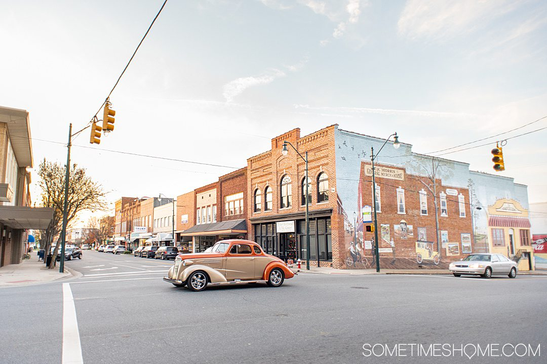A vintage car drives past a downtown street with a mural on the side of a building in Asheboro, NC.