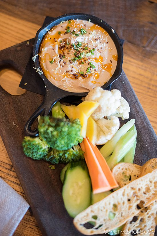 Close up of a rectangular plate of hummus and vegetables at Steelbach, one of the Armature Works restaurants in Tampa.