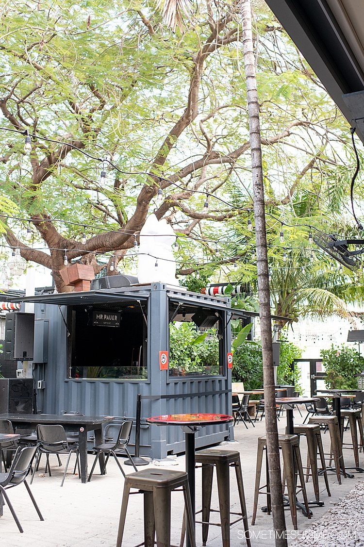 Outdoor patio of 1-800-Lucky in Wynwood, Miami in Florida with a grey kiosk and tables outside.