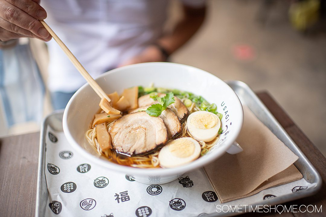 A bowl of tonkatsu ramen with an egg, meal, green onions and chopsticks on the left at 1-800-Lucky in Wynwood, Miami, FL.