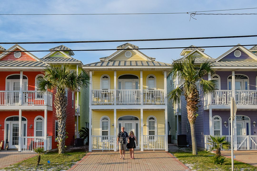 Three colorful homes with a balcony, and a couple walking in the center.