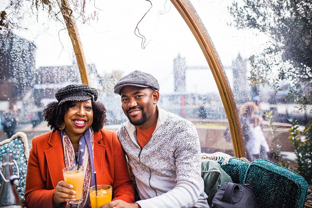 Couple inside a clear bubble with rain on it. They're holding two glasses of orange juice.