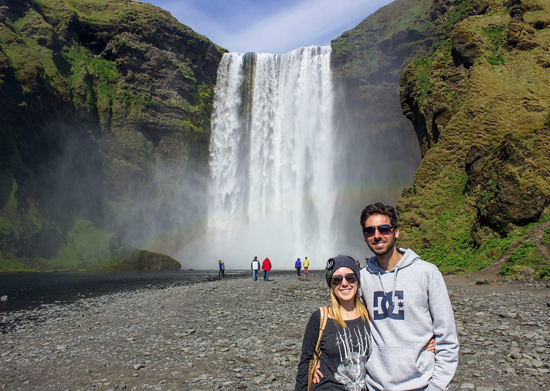 Couple in the foreground to the right of the image with a waterfall and rainbow in the background.