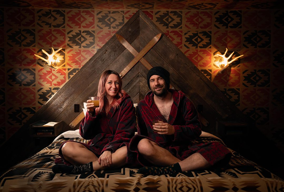 Couple sitting cross-legged on a bed in dark red bathrobes in a woodsy-feeling, darkly lit room.