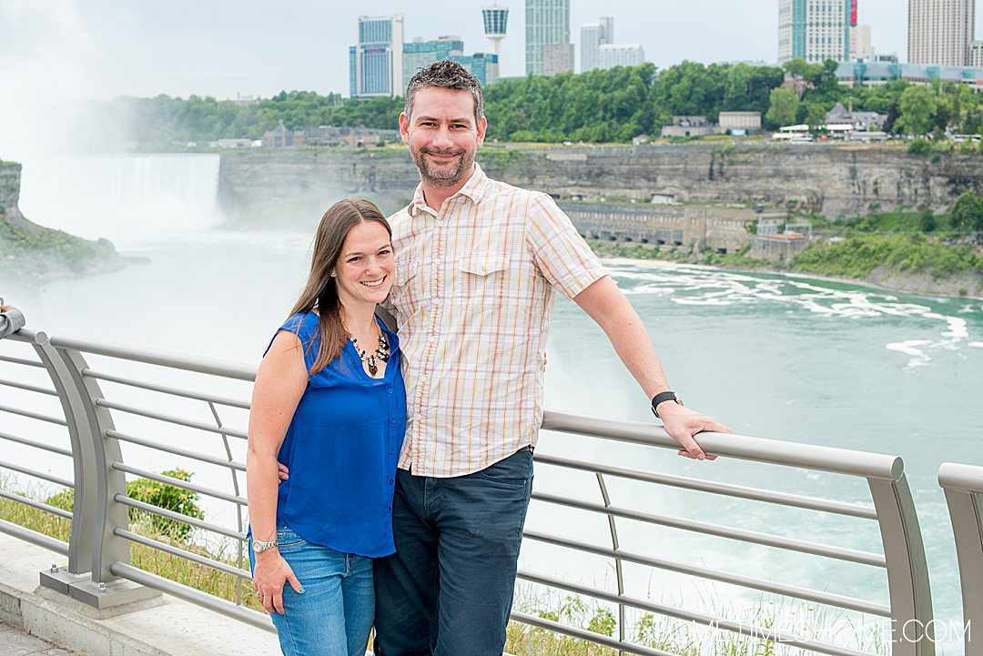 Couple travel bloggers, a female and male, standing in front of Niagara Falls during summer.