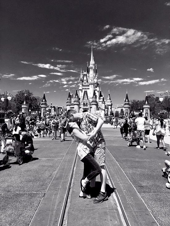 Couple kissing in front of the Magic Kingdom in a black and white photo.