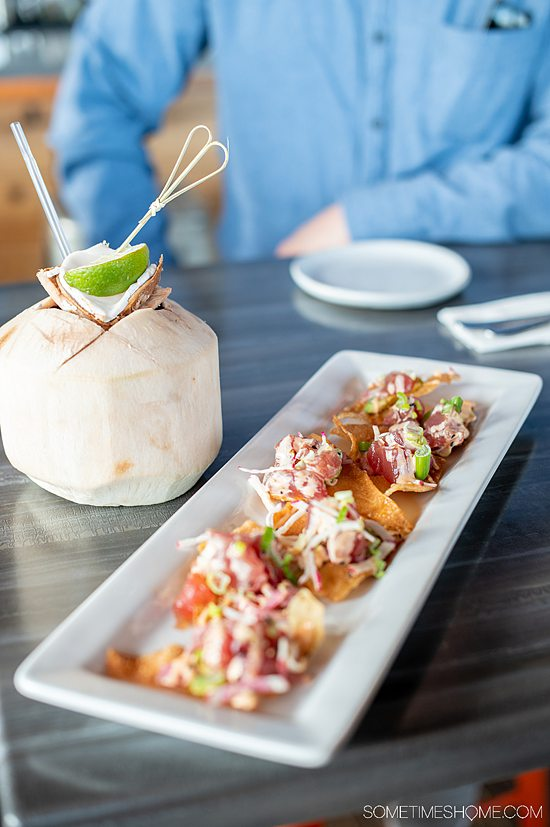 A rectangular plate with tuna-topped nachos and a coconut drink next to it with a straw and a lime at Spice, a restaurant in Fort Mill, SC.