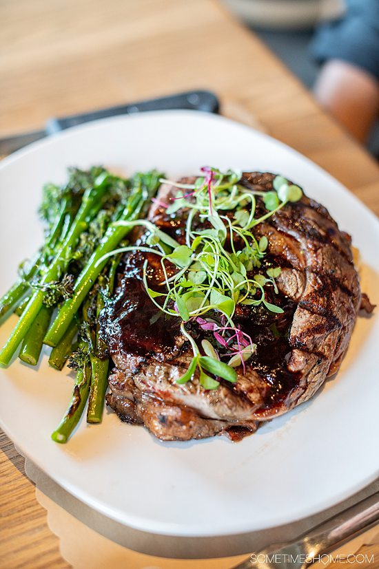 Plate of steak topped with micro greens and broccolini on the side at Napa Kingsley, at Fort Mill, SC.