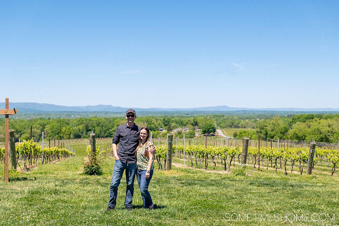 A man and woman in front of a vineyard, at one of the Yadkin Valley wineries in North Carolina.