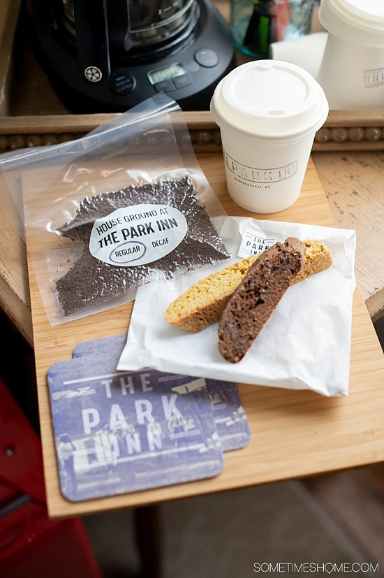 Biscotti, coffee grinds in a bag and a coffee cup on a table at The Park Inn.