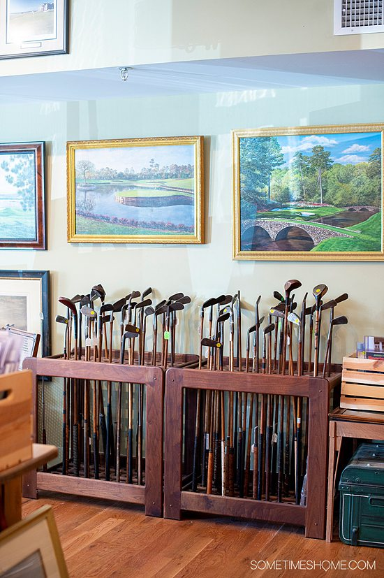 Interior of Old Golf Shop in Pinehurst, NC, with paintings and a rack of old golf clubs.